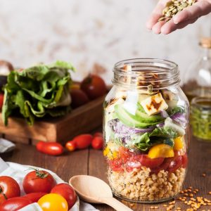 A person preparing a healthy meal in a mason jar