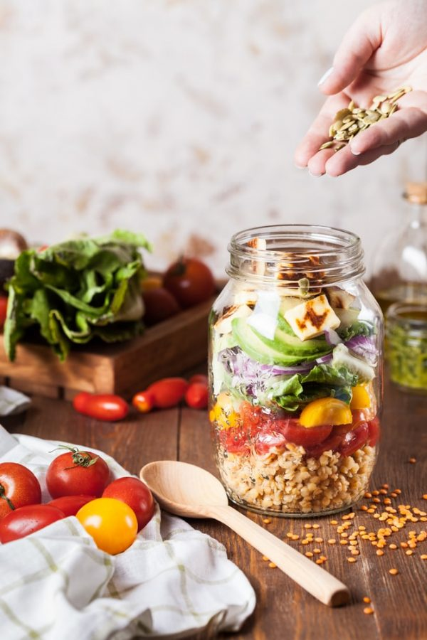 A person preparing a healthy meal in a mason jar